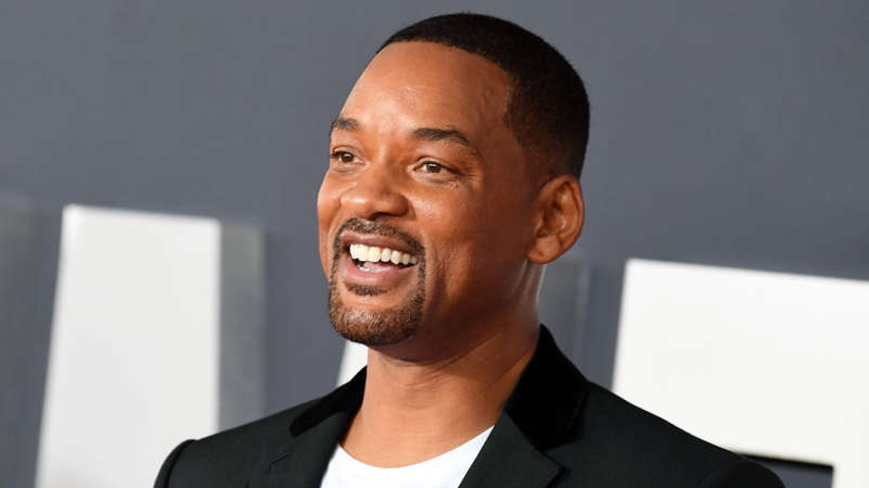 Will Smith wearing a suit and tie smiling at the camera