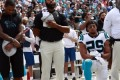 Panthers' Reid returns, kneels during national anthem