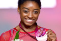 Simone Biles fights through kidney stone pain to triumph at competition