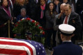 Bob Dole helped out of his wheelchair to salute George H.W. Bush