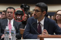 A person dressed up like the Monopoly man is sitting behind Google's CEO as he testifies in Congress