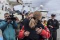 British sailor embraces her mother as she returns to shore in Chile days after rescue from yacht which capsized during solo round-the-world race