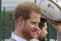 Proud father Prince Harry revealed four-month-old son Archie is 'getting so big' while speaking to schoolchildren at a rugby event