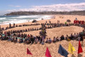 Extinction Rebellion activists form logo on sand at Bondi Beach