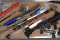 Calgary man faces 25 charges after guns, machetes, axes, drugs seized from homes