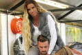 Katie Price carried around by boyfriend Carl Woods as she continues recovery for broken legs